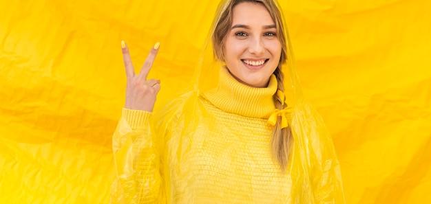 Gelukkige vrouw die vredesteken doet