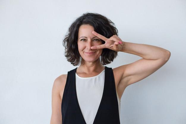 Gelukkige vrouw die vredesteken toont