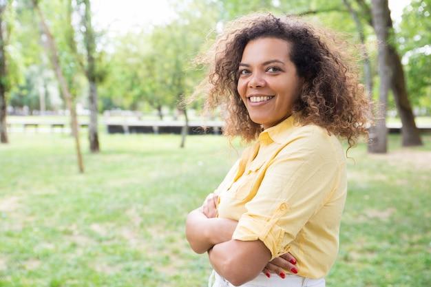 Gelukkige vrouw die wapens houden gekruist en bij camera in park stellen