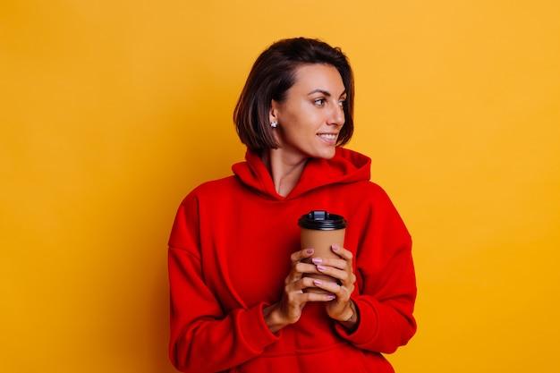 Gelukkige vrouw die warme winterkleren draagt, verwarmt zich met kop hete koffie