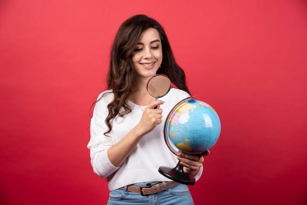 Gelukkige vrouw die wereldbol met vergrootglas bekijkt. hoge kwaliteit foto