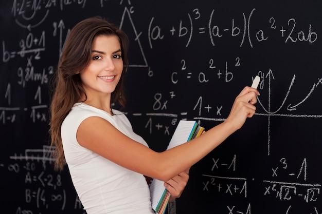 Gelukkige vrouw die wiskundige problemen oplossen