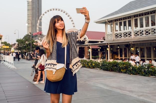 Gelukkige vrouw die zelfportret op reuzenradachtergrond maakt, die aan rivierfront loopt.