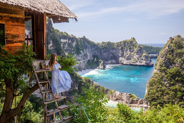 Gelukkige vrouw die zich dichtbij boomhuis bij gezichtspunt duizend eiland nusa penida bevinden
