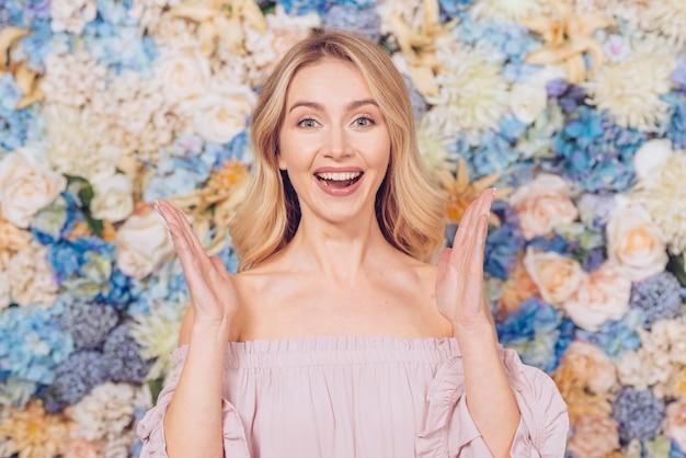 Gelukkige vrouw die zich op bloemenachtergrond bevindt