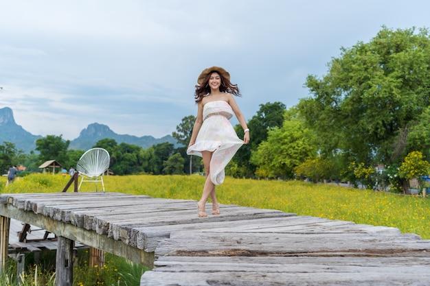 Gelukkige vrouw die zich op houten brug met het gele gebied van de kosmosbloem bevinden
