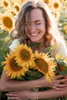Gelukkige vrouw die zonnebloemen koestert