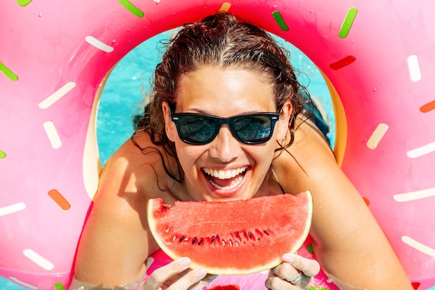 Gelukkige vrouw die zonnebril met rode watermeloen draagt geniet in zwembad met roze rubberring