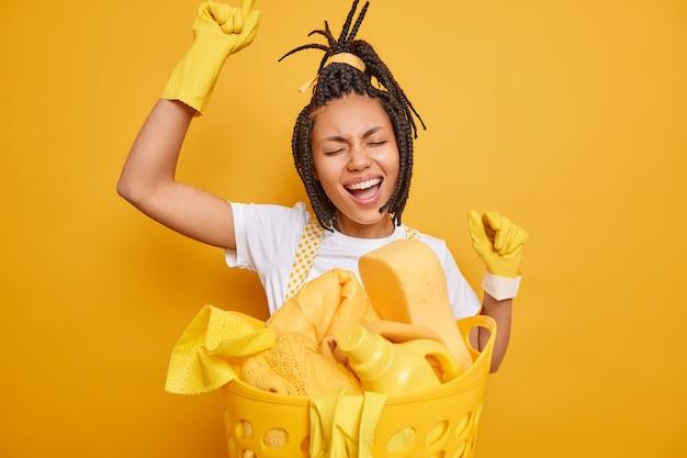 Gelukkige vrouw dienstmeisje danst zorgeloos houdt armen omhoog poses in de buurt van wasbak heeft plezier terwijl het doen van huishoudelijke klusjes zingt lied mee geïsoleerd over levendige gele achtergrond. huishoudconcept