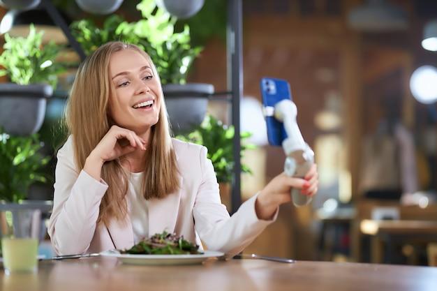 Gelukkige vrouw doet selfie met moderne telefoon in café