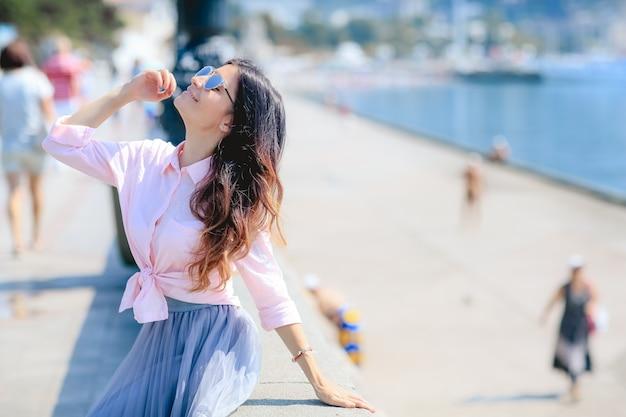 Gelukkige vrouw door te poseren in de buurt van de zee in een hete zomerdag.