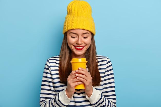Gelukkige vrouw draagt een stijlvolle gele hoed en gestreepte trui, houdt afhaalkoffie vast, heeft rode geschilderde lippen, geniet van aromatische drank