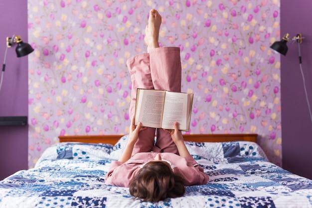 Gelukkige vrouw draagt pyjama en ontspant thuis en leest een boek. blijf thuis. quarantaine pandemie
