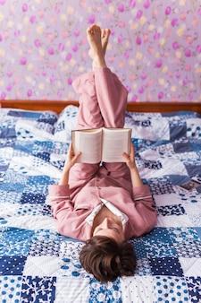 Gelukkige vrouw draagt pyjama en ontspant thuis en leest een boek
