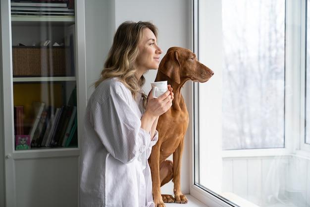 Gelukkige vrouw eigenaar en hond zittend op de vensterbank, kopje koffie te houden, kijkend door het raam