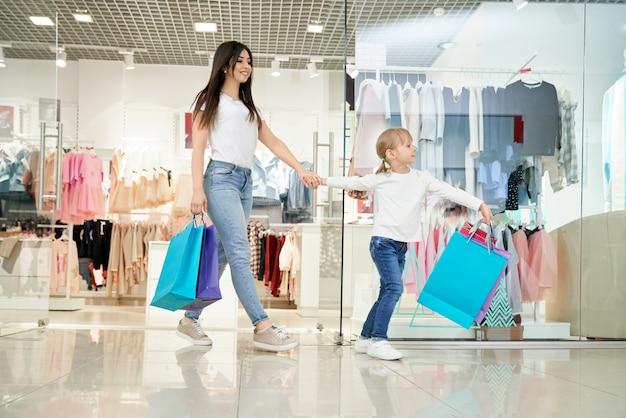 Gelukkige vrouw en dochtertje uitgaan van winkel in winkelcentrum
