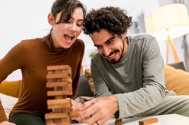 Gelukkige vrouw en echtgenoot die een houten torenspel spelen