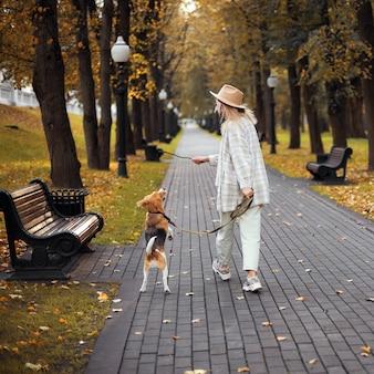 Gelukkige vrouw en hond beagle samen buiten spelen.