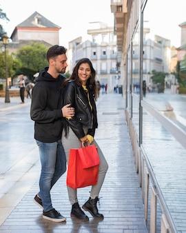 Gelukkige vrouw en jonge man op straat dichtbij etalage