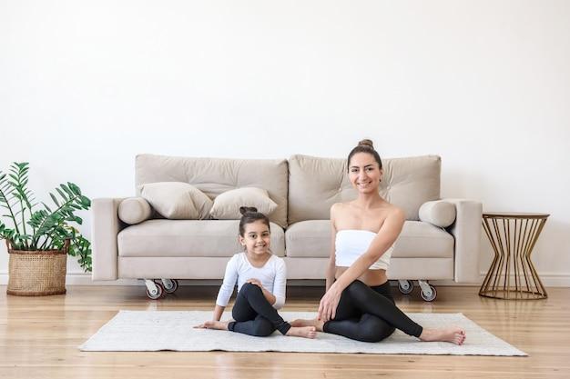 Gelukkige vrouw en kindmeisje die yoga samen thuis op het tapijt doen