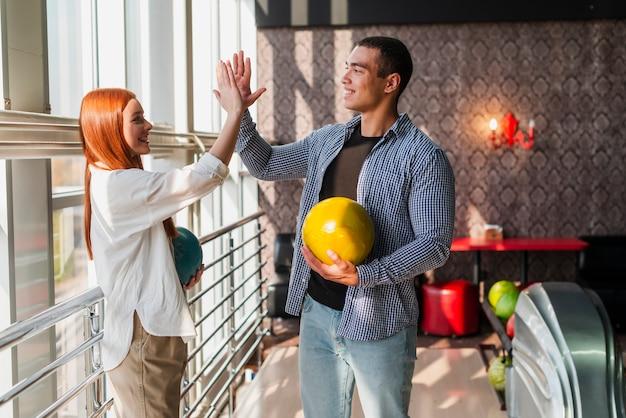 Gelukkige vrouw en man die kleurrijke kegelenballen houden