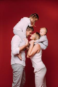 Gelukkige vrouw en man die zich op rood bevinden met hun neuzen aanraken. kinderen zitten op hun schouders.