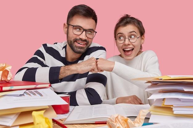 Gelukkige vrouw en man geven elkaar een vuistslag, werken als een vriendelijk team, komen overeen om samen te werken, omringd met handboeken en papieren met gegevens en grafieken