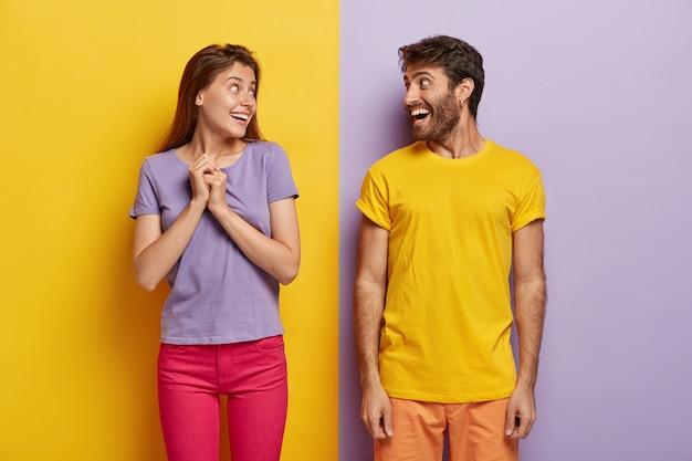 Gelukkige vrouw en man kijken elkaar graag aan, gekleed in levendige zomerkleding, hebben plezier