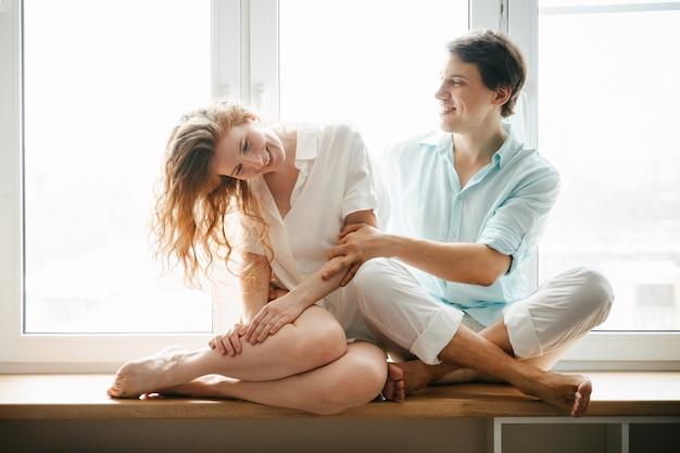 Gelukkige vrouw en man knuffelen in de buurt van venster in huis op valentijnsdag