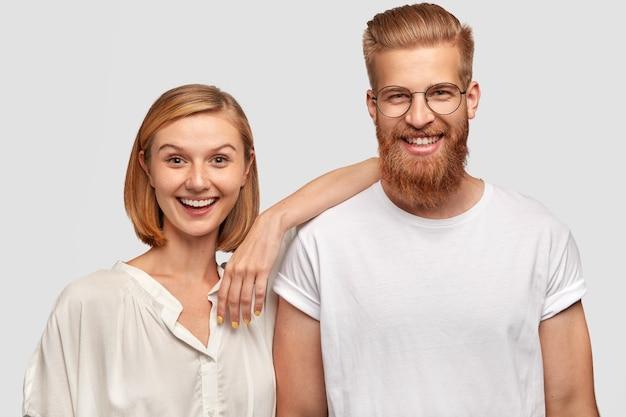 Gelukkige vrouw en man paar gekleed in casual witte kleding, hebben positieve uitdrukkingen