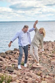 Gelukkige vrouw en man wandelen langs de kust