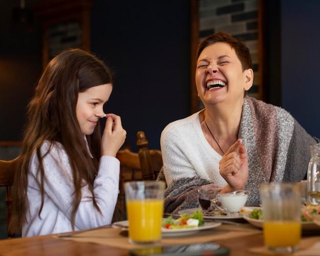 Gelukkige vrouw en meisje die samen eten