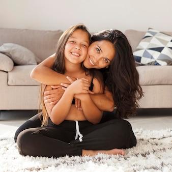 Gelukkige vrouw en meisjeszitting op tapijt