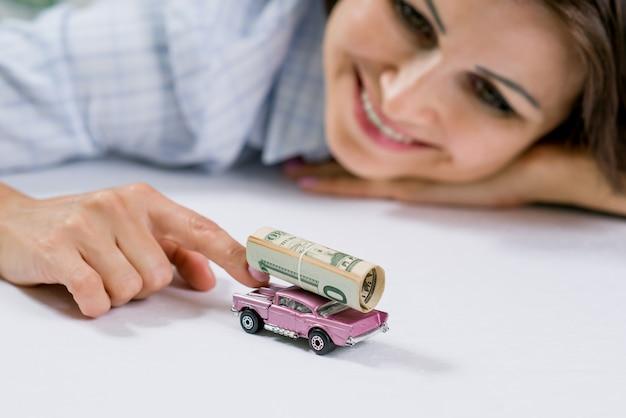 Gelukkige vrouw en speelgoedauto, geldbankbiljetten