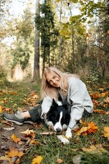 Gelukkige vrouw en zwart-witte border collie-hond in de herfstbos