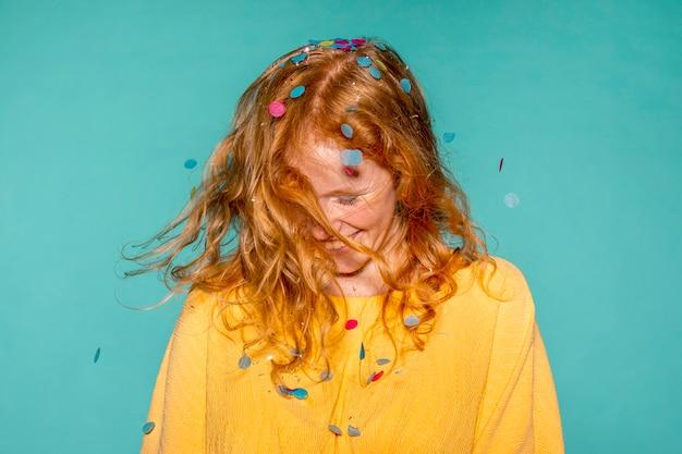Gelukkige vrouw feesten met confetti in haar haar