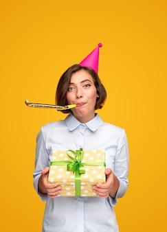 Gelukkige vrouw feliciteren met verjaardag cadeau geven en blazen partij hoorn camera kijken op gele achtergrond