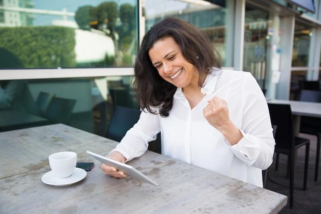 Gelukkige vrouw gebruikend tablet en vierend succes in openluchtkoffie