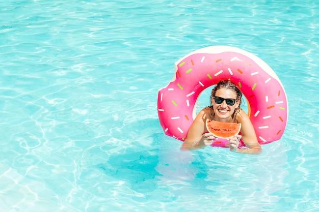 Gelukkige vrouw geniet in zwembad met roze rubberen ring