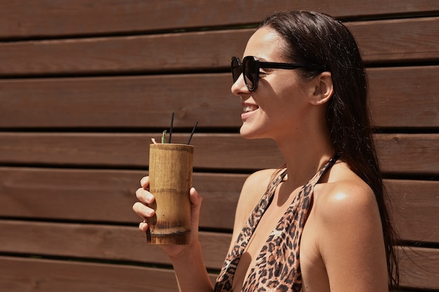 Gelukkige vrouw genieten van exotisch drankje in bar, glimlachend in de verte kijken, zwarte zonnebril en zwemkleding dragen