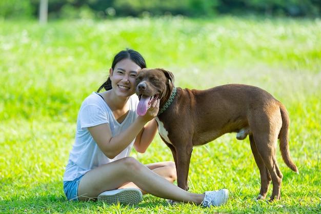 Gelukkige vrouw genieten van haar favoriete hond in het park.