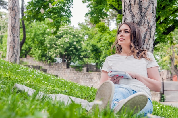 Gelukkige vrouw genieten van het leven in het veld met bloemen. natuur schoonheid, blauwe bewolkte hemel en kleurrijke veld met bloemen. outdoor lifestyle. freedom concept. vrouw op zomer veld
