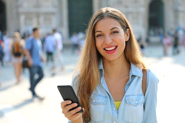 Gelukkige vrouw glimlachend en wandelen in de straat met behulp van een smartphone