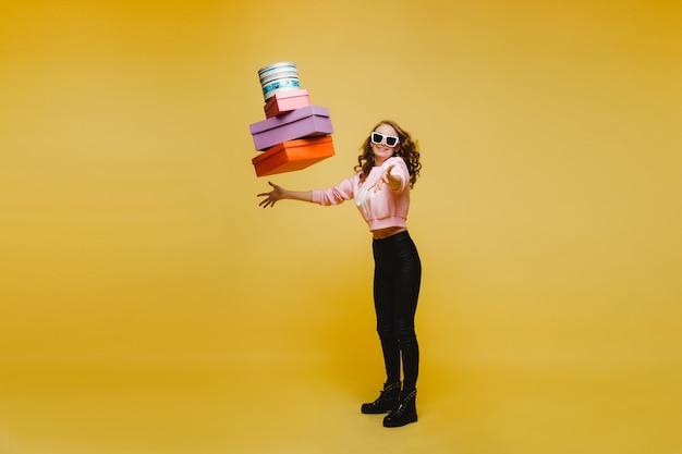 Gelukkige vrouw gooit kleurrijke kartonnen dozen na het winkelen