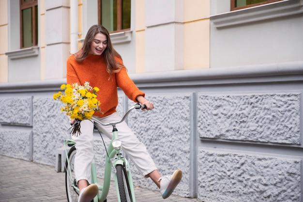 Gelukkige vrouw haar fiets buiten met boeket bloemen