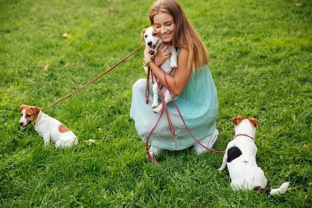 Gelukkige vrouw haar honden aaien tijdens een wandeling in het park