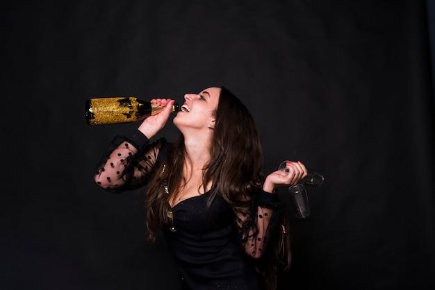 Gelukkige vrouw het drinken champagne van fles