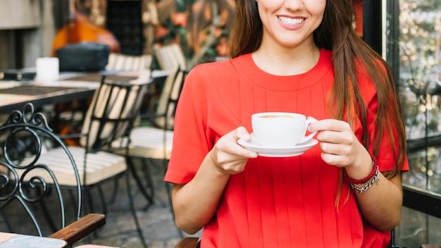 Gelukkige vrouw het drinken koffie in caf�