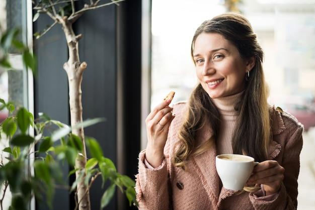 Gelukkige vrouw het drinken koffie met cake