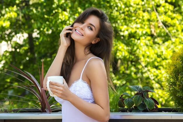 Gelukkige vrouw het drinken koffie op het balkon of in de tuin